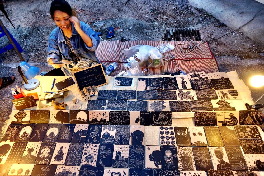 An artist selling her charming linocut postcards