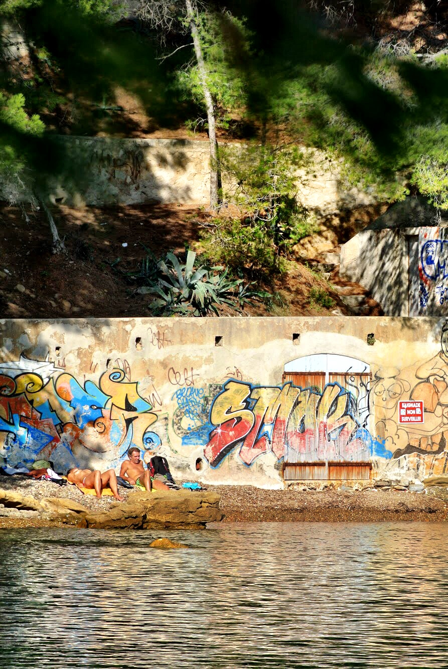 Graffiti decorates the walls along the thin slivers of rocky beaches