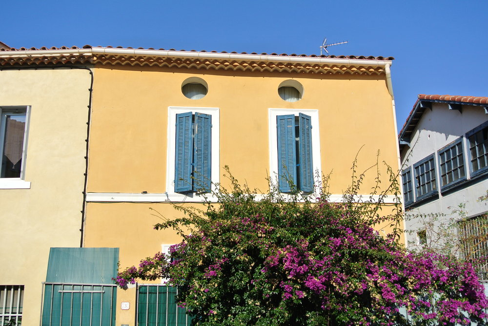 Many of the buildings of Provence are pastel-colored, with shuttered windows