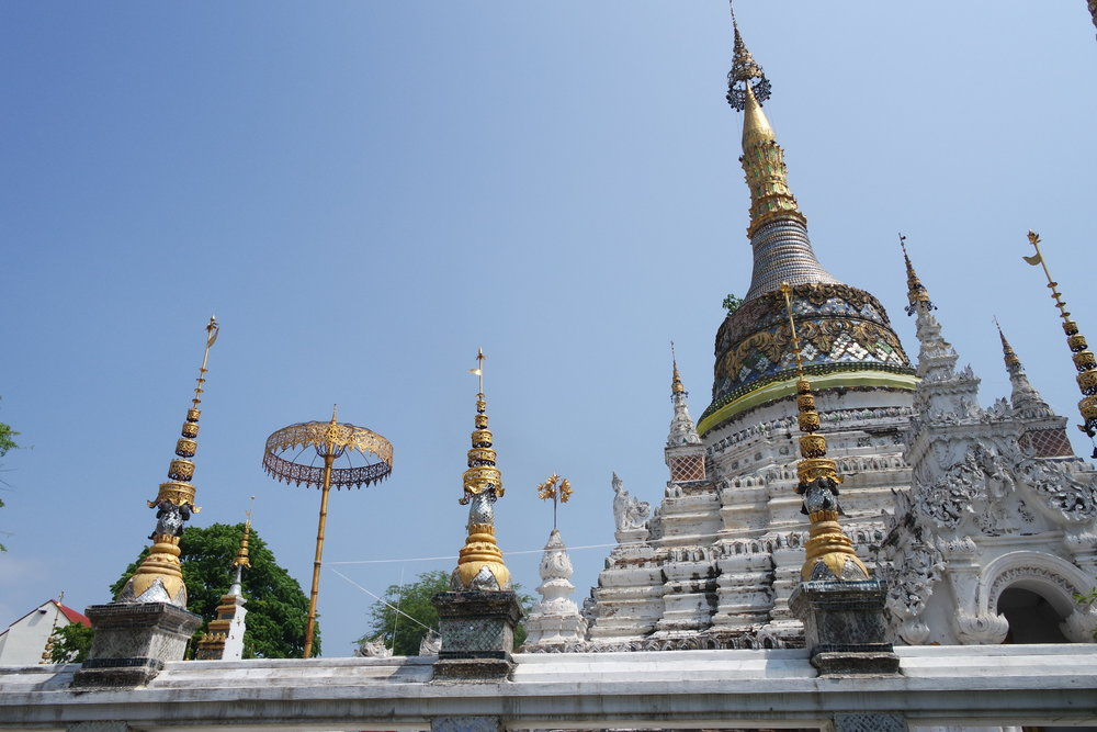 The beautiful whitewashed chedi at Wat Saen Fang is surrounded by gold umbrellas and offeratory fires