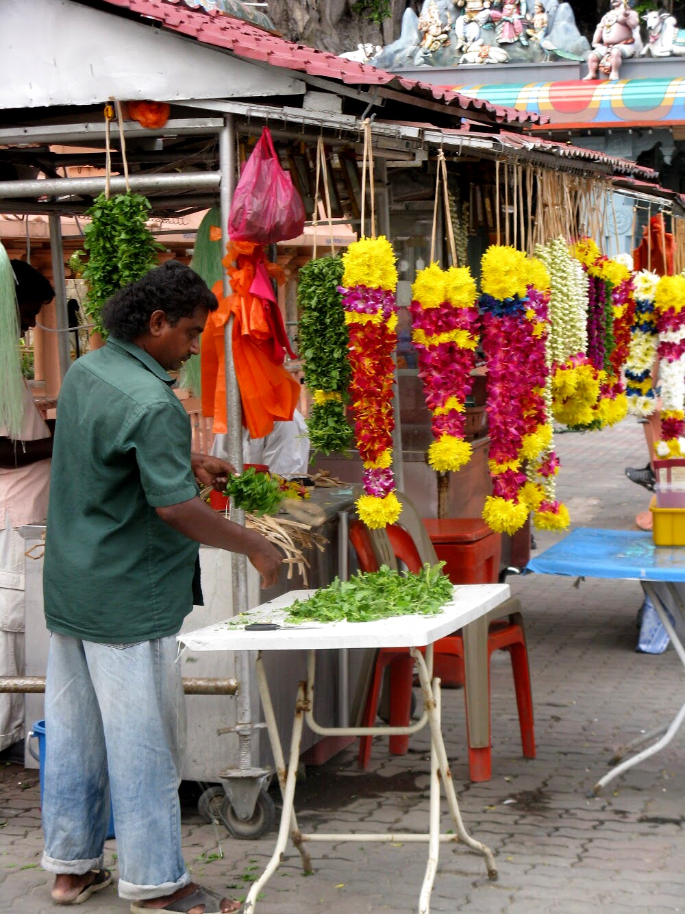 At the base of the stairs, vendors sells floral offerings to the gods