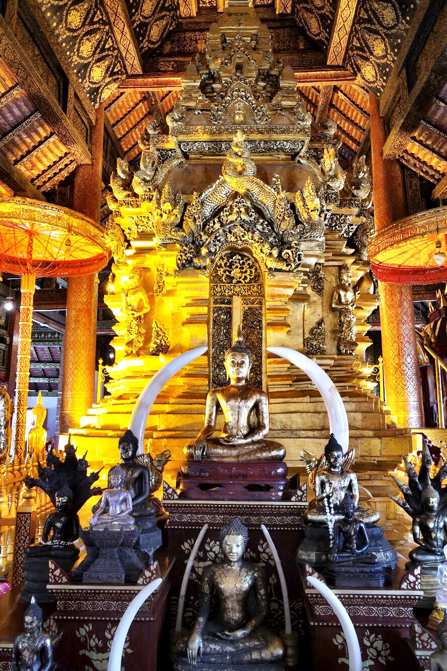 The focal point of the assembly hall features numerous Buddhas, elephant tusks and an elaborately carved centerpiece