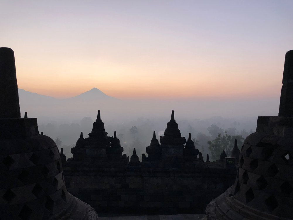 Volcanos can be seen in the distance — in fact, violent eruptions in the past covered the entire temple in ash for 800 years