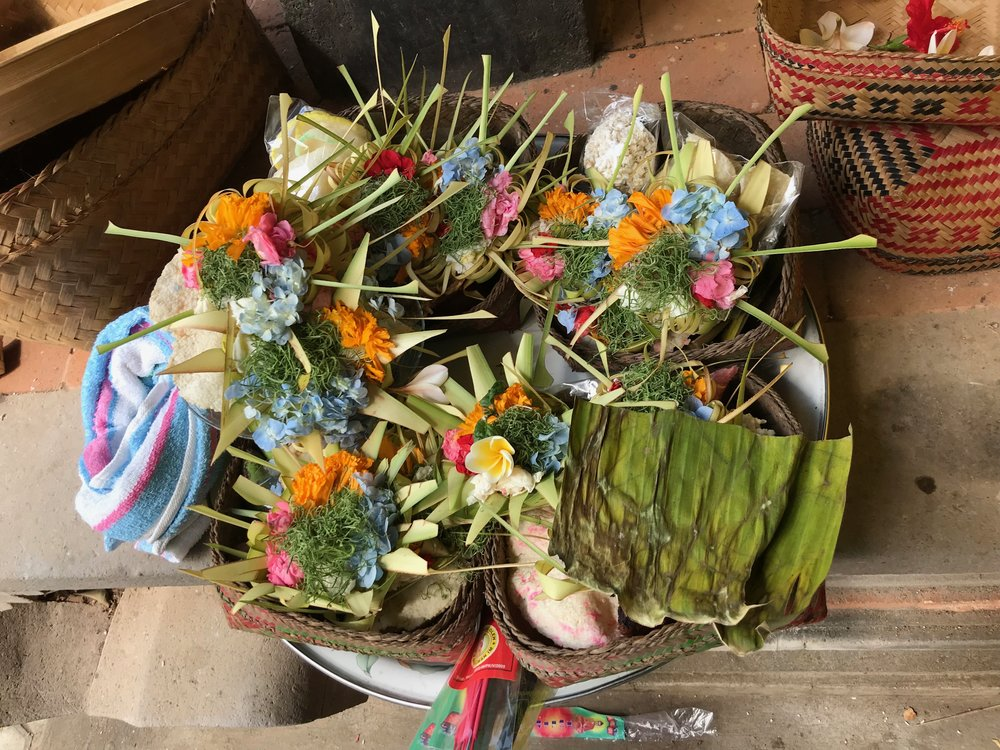 Worshippers create small offering dishes filled with flowers and food