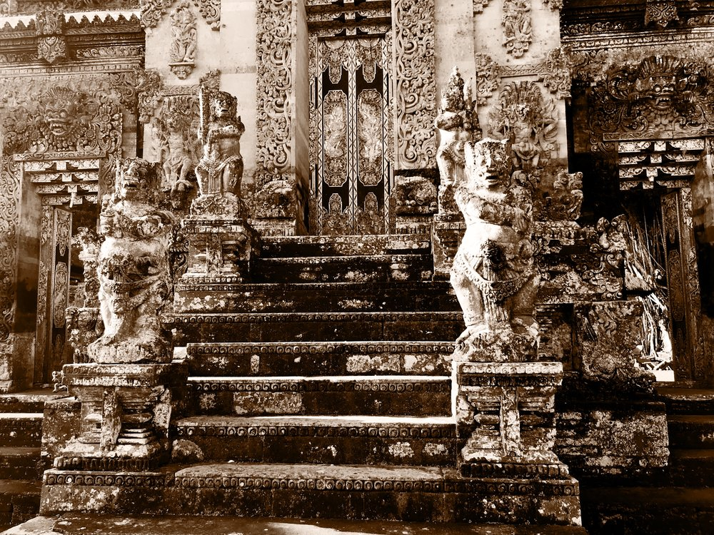 Weather-worn statues, ornate detailing and lichen-covered stone are typical at Balinese temples