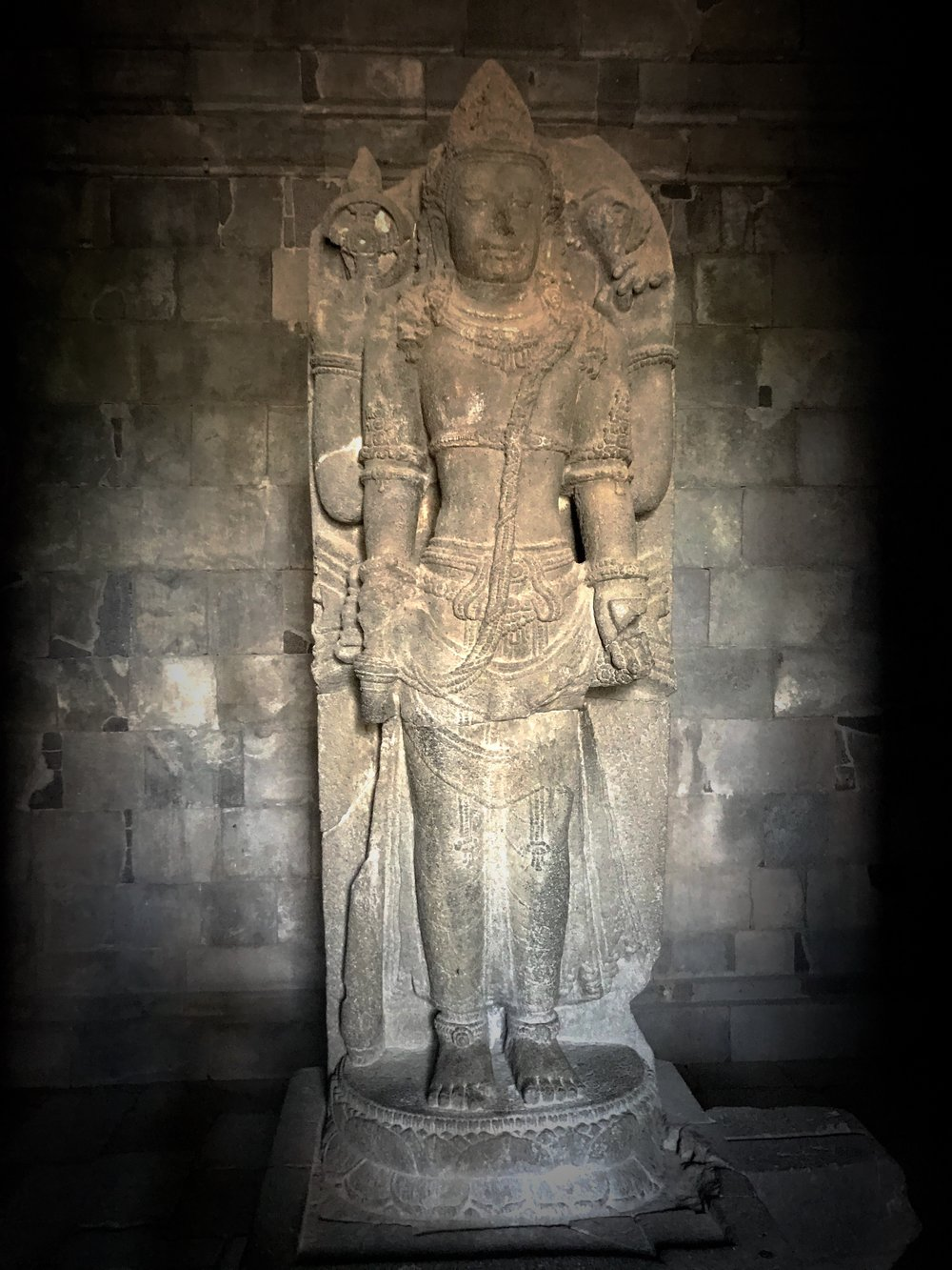 Vishnu the Protector holds a discus and conch shell