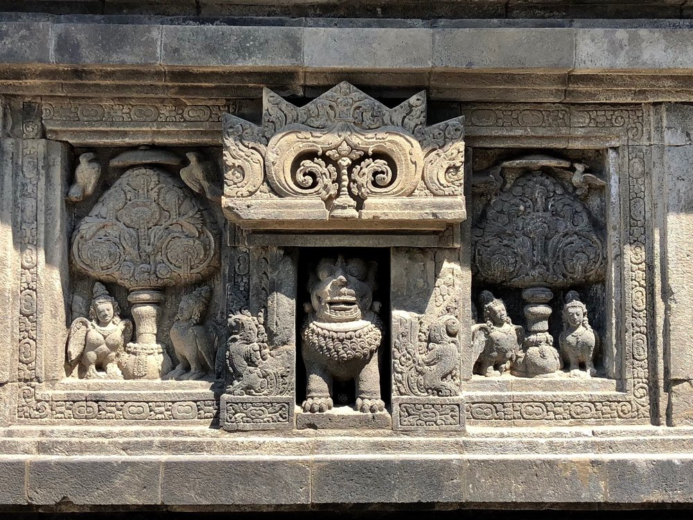 A lion sits within a small niche flanked by half-woman and half-bird kinnara