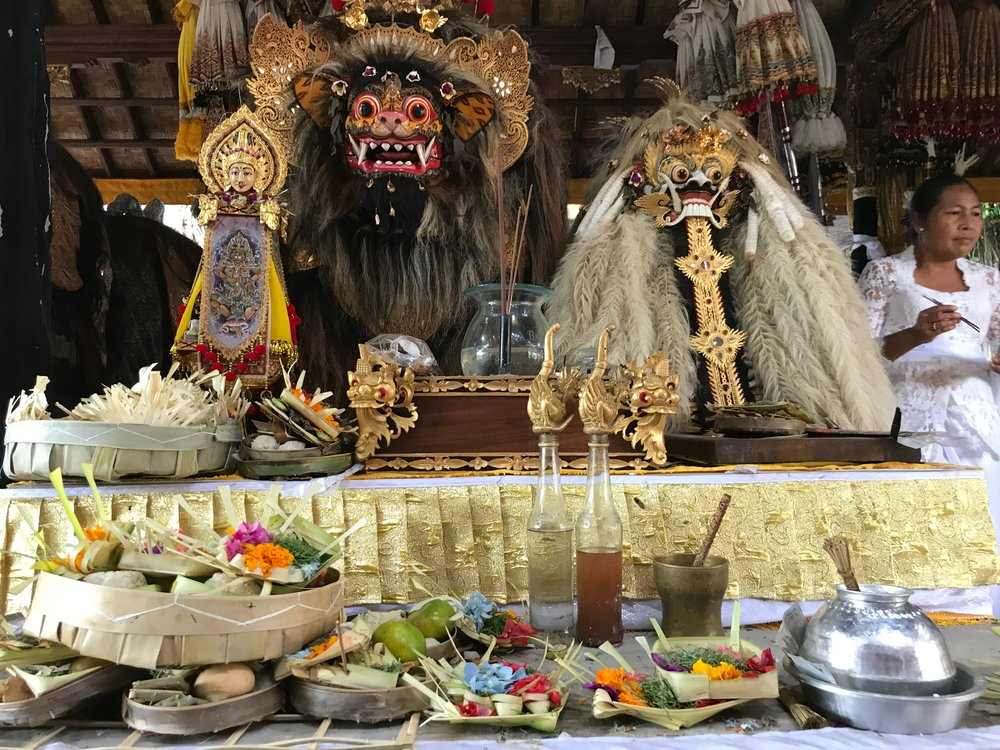 The Hindus of Bali offer flowers and fruit to thank Barong for protecting them. The mask on the left is the form of a macan, or tiger