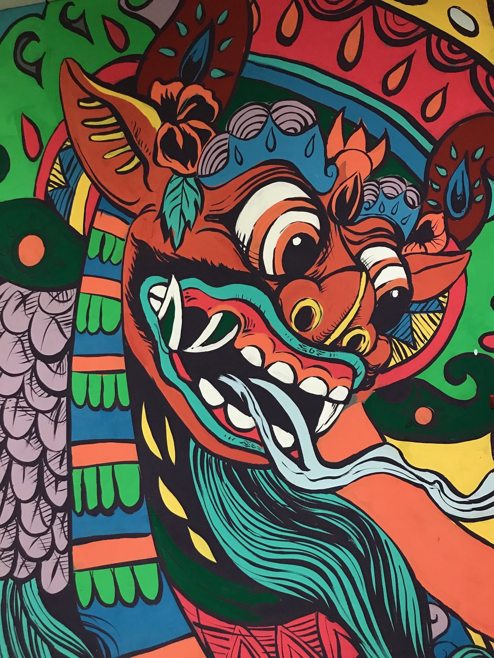 Barong bids visitors farewell in this mural at the Denpasar airport