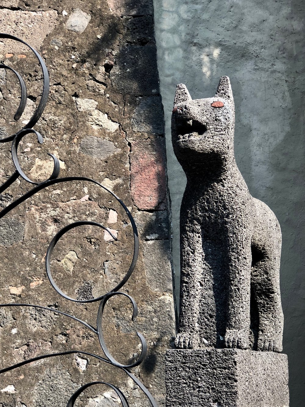 Dogs carved from volcanic rock adorn the house