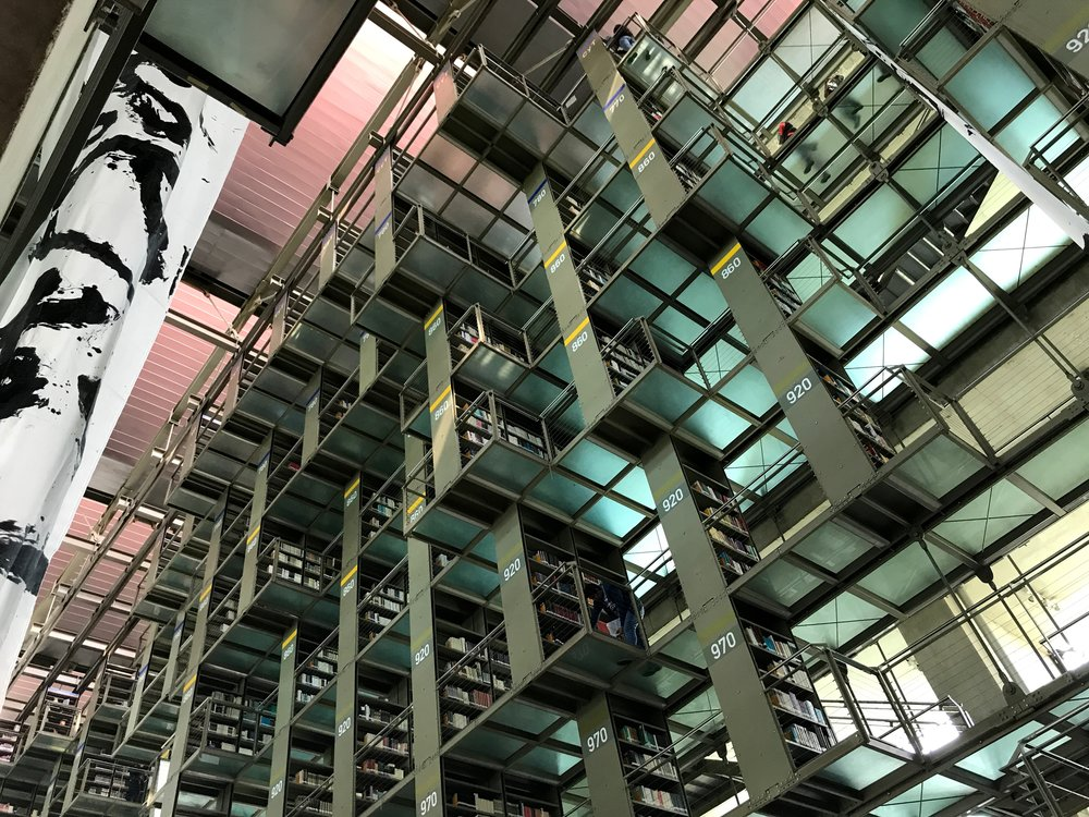 Greenish-blue semitranslucent walkways connect the stacks