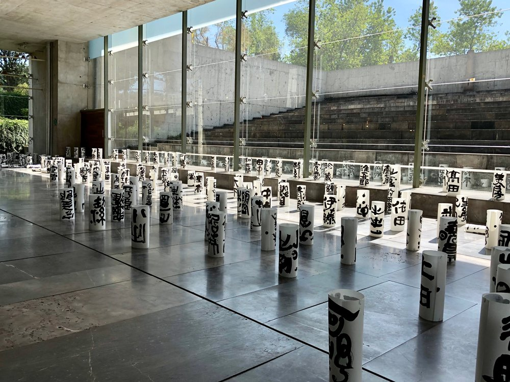 A forest of paper cylinders with Japanese kana characters on display at the entrance