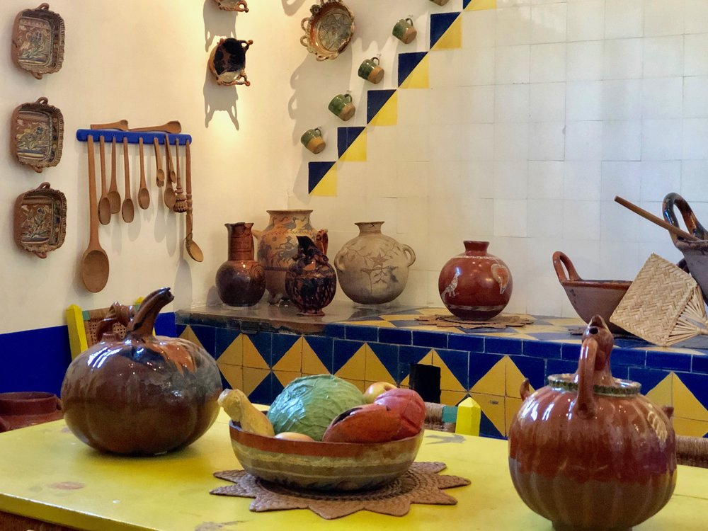 The neutral tones of earthenware pottery pair nicely with the bright blue and yellow tiles