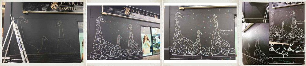 Giraffe Mural -  When we were at the AGHA trade show in August this year, Dianne from  Dártagnan  (an amazing gift shop in Puckle Street Moonee ponds) loved our big giraffe that we had blown up on our wall. They have a black wall on the outside of the back of their store that was a magnet for the odd bit of graffiti and Dianne hoped that by putting a mural there it would be a deterrent and something fun for people to interact with too.  I created a draft first on black paper to draw up the picture to scale as it would be on the wall. Roy, Dianne's other half, helped put up the gridlines on the wall and then I got to work drawing up the three giraffes and the butterflies. It was created using chalk and then Posca pens in various colours. It was a hot and windy 38 degree day when I created it, but it was a truly amazing and fun experience.  I'm so grateful to Dianne for giving me chance to have a go at my first mural!  If you want to have a look at it in real life – it's on Hall St in Moonee Ponds!