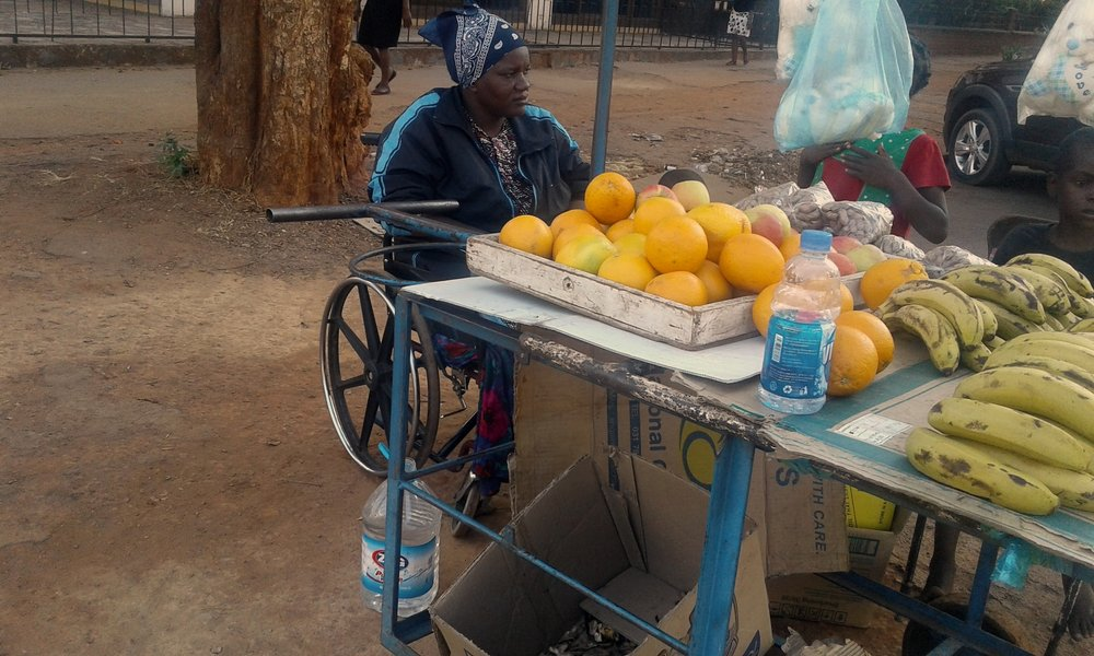 Disabled women at her informal fruit and vegetable stall