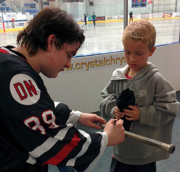 Colby Bannister Signs an Autograph for a young fan.  Photo Courtesy of Janelle Jaksitz