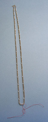 Center front of chain necklace marked with thread