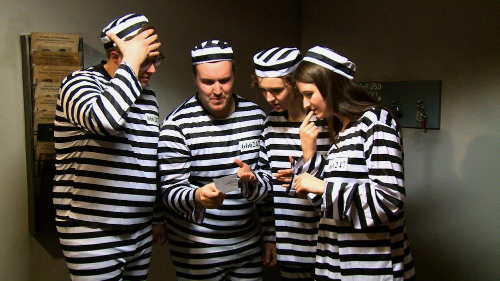 Luc, Derrek, Laura et Chloé doivent résoudre un énigme pour s'échapper de leur prison.  Luc, Derrek, Laura and Chloé must solve a riddle to escape their prison.