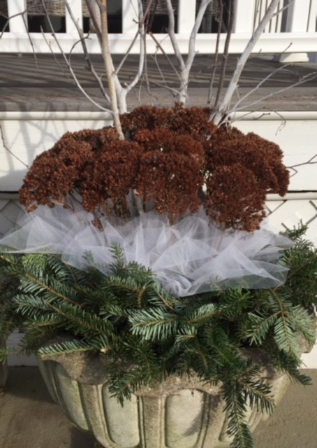 - This pair of flouted concrete pots uses dried Sedum from the perennial garden, Birch twigs, a ready-made spruce wreath, and a little white tulle to emulate snow.