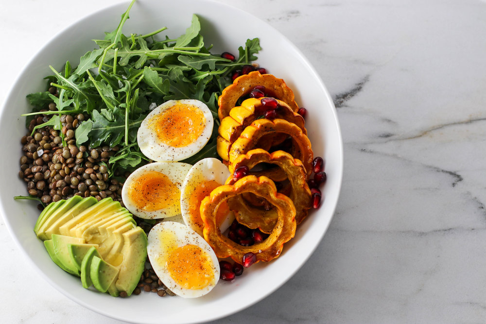 Nourish Bowl #1 - Lentils, arugula, maple roasted delicata squash, pomegranate seeds, avocado, two 7-minute eggs, a drizzle of lemon olive oil, black pepper, and a sprinkling of Maldon sea salt.