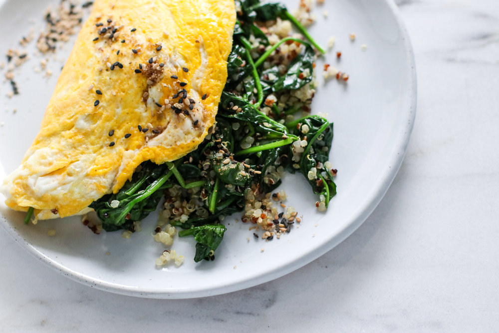 Omelet with Spinach and Quinoa - On Mondays I take a 9:30am spin class, which means I usually don't have my first big meal until almost 11am. And as a refuel, I know my body needs protein and a little bit of carb.I quickly sautéed the spinach and quinoa in a pan with a touch of coconut oil. Then removed them and cooked my eggs with a touch more oil - I love the slight sweetness coconut oil adds when cooked with eggs.