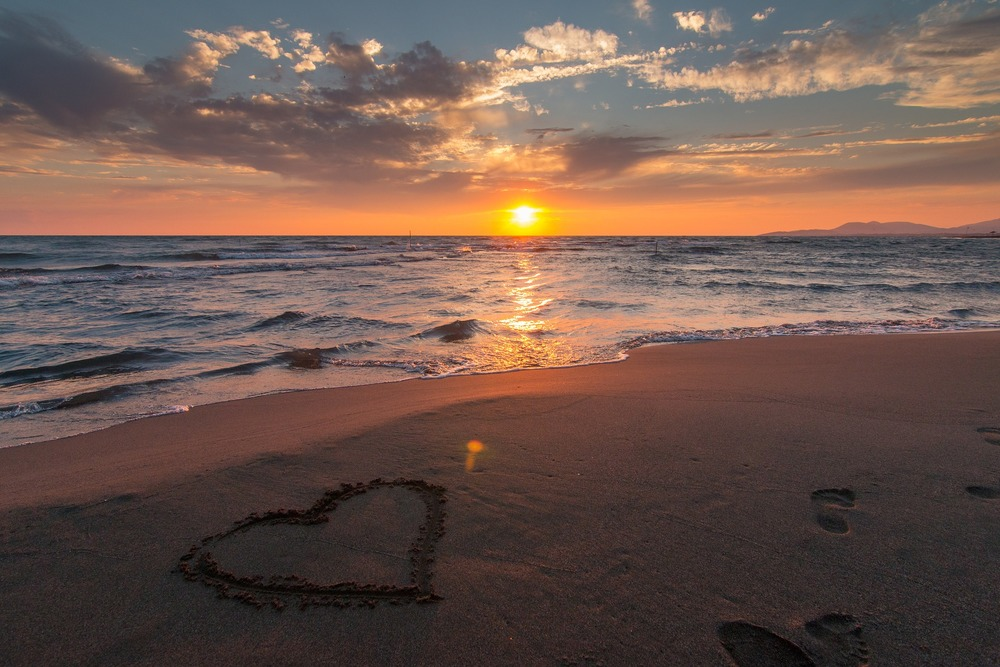 heart on sand in sunrise