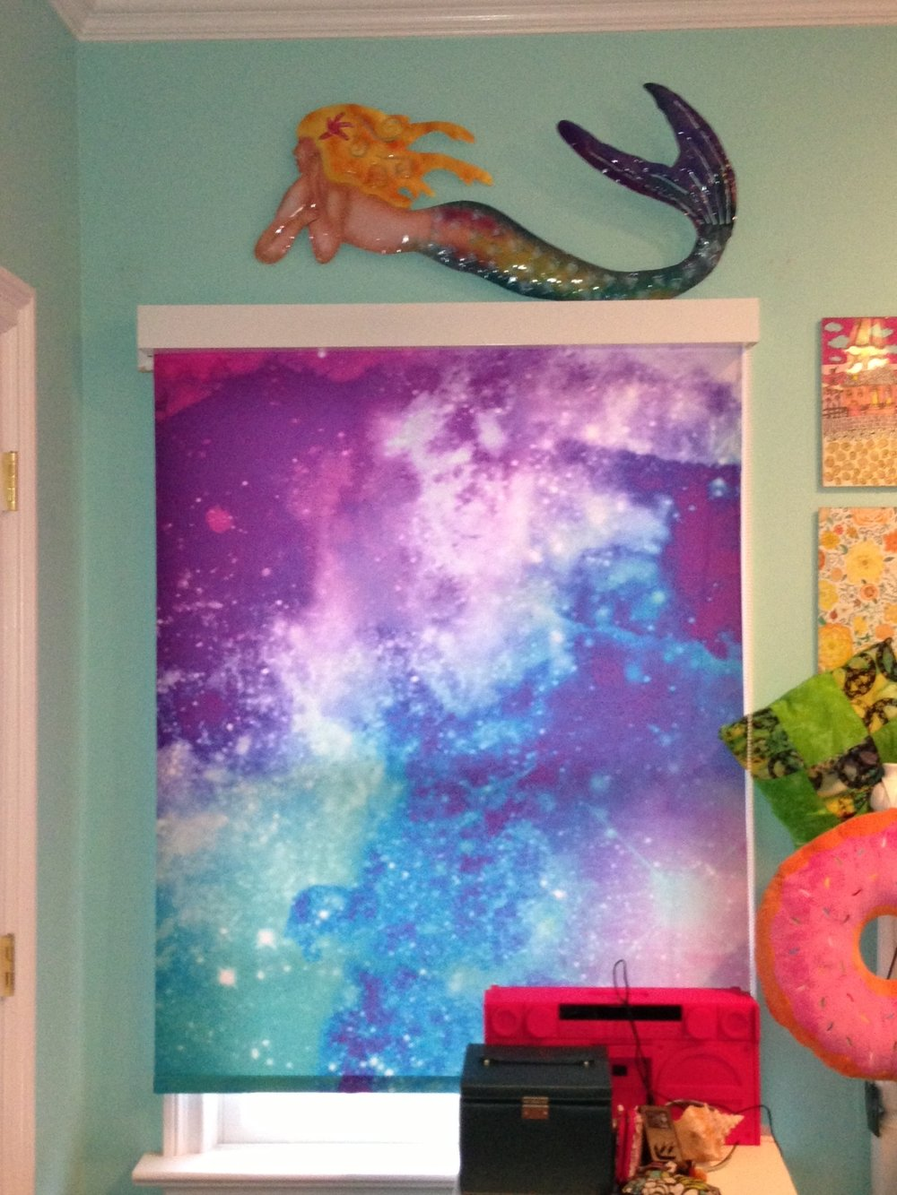 Whimsical, galaxy window shades in child's room.  White fascia used to create clean top border.