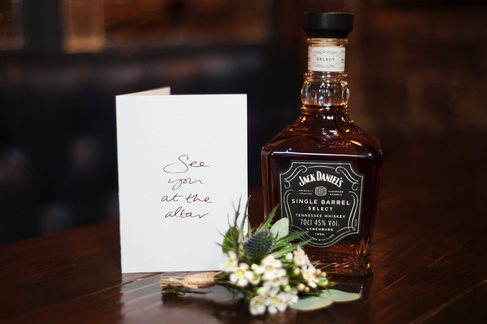 text from a friend card says See You At The Altar alongside a bottle of Jack Daniels and a buttonhole for the groom