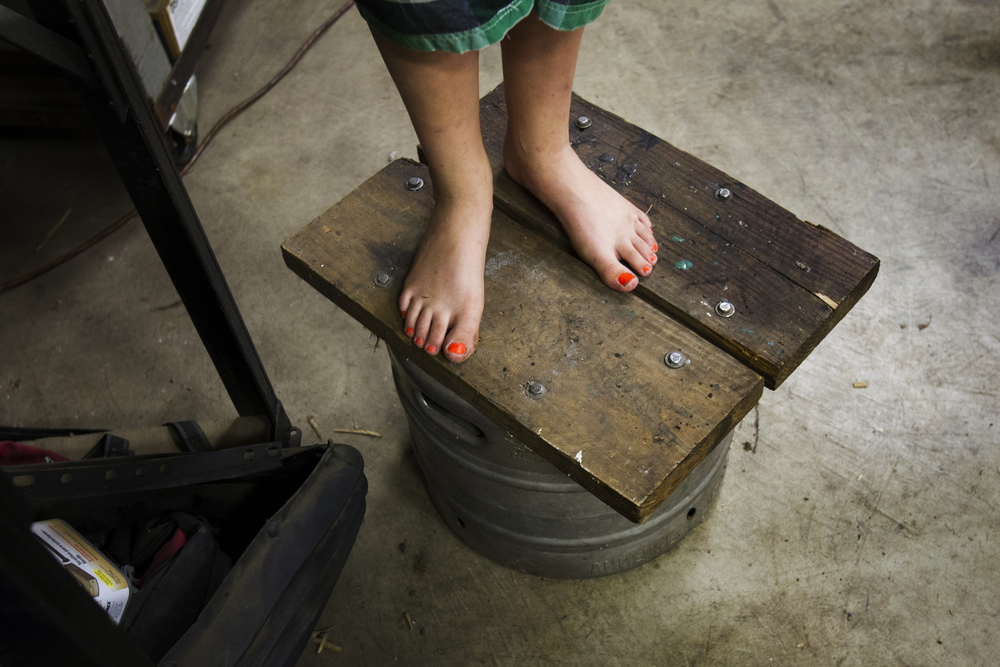 Sydnie Abke, 10, stands barefoot on a bucket in the garage where her father, Russ, stores the family's farm equipment on their property near Pemberville.