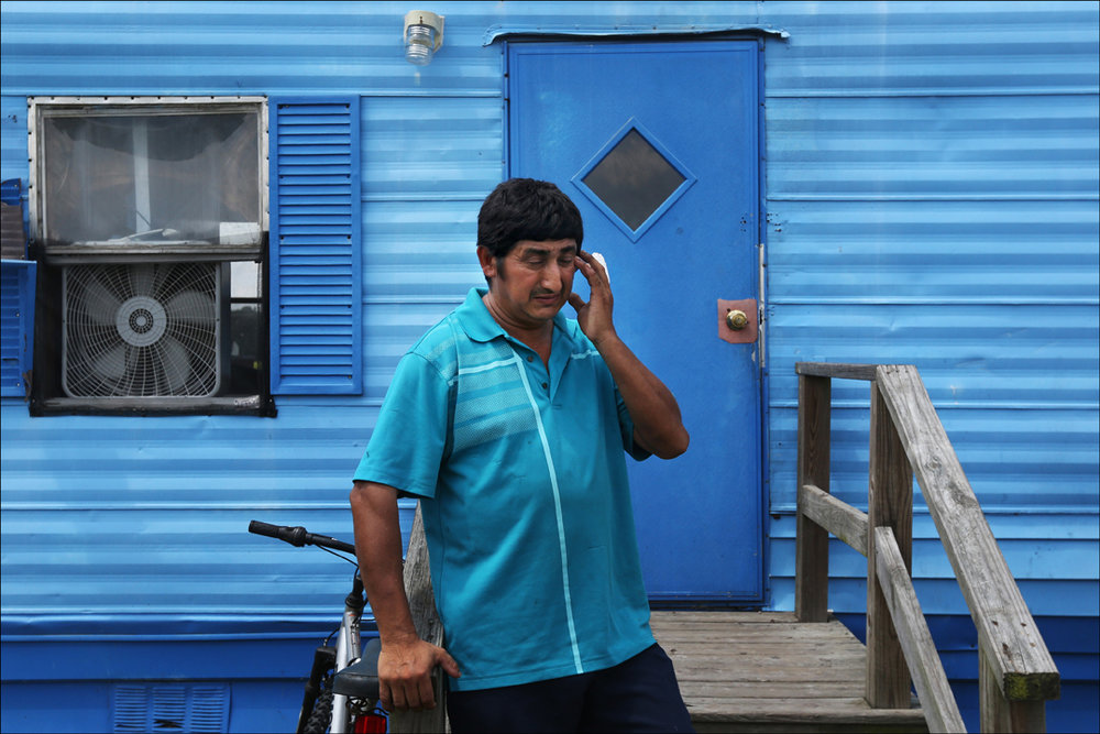 Santiago Garcia, a tobacco worker from Guatemala, pauses as he speaks of his inability to work while standing near the single wide trailer where he and four other men near Dudley, North Carolina. Garcia, who had to turn the deed to his property in Guatemala to the smuggler who helped him get the the U.S., had part of his finger amputated recently in an on-the-job accident. His employer pays no workman's compensation, and Garcia is going to be soon unable to make rent. Facing the potential of deportation and the subsequent loss of his property in Guatemala, Garcia turned to the Farm Labor Organizing Committee, AFL-CIO (FLOC) for help. They are engaged in a campaign to unionize North Carolina tobacco workers.