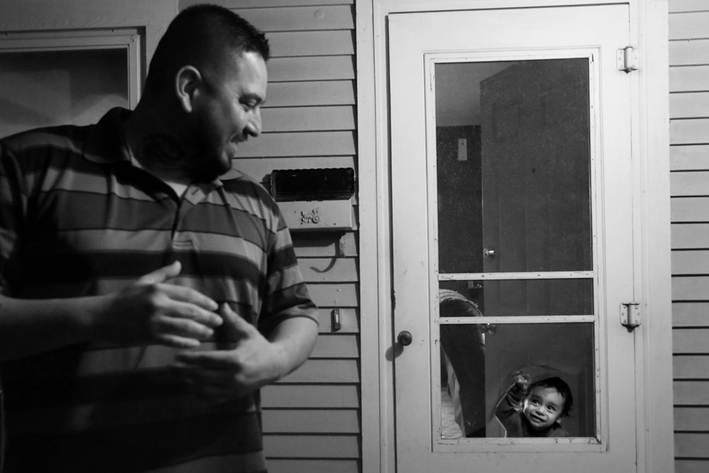 Rojelio Sanchez, left, smiles back as his two-year-old son Rojelio III, peers through a hole in the screen door at the family's home in Napoleon. Since being released from prison after serving 11 years for attempted murder, Rojelio has made it his goal to provide a better life for his family. He and his wife Rebecca recently relocated their family of six from North Toledo to Napoleon. Sanchez works as the manager of Evergreen Seed Supply, where he does everything from managing the warehouse, to administrative work to truck driving.