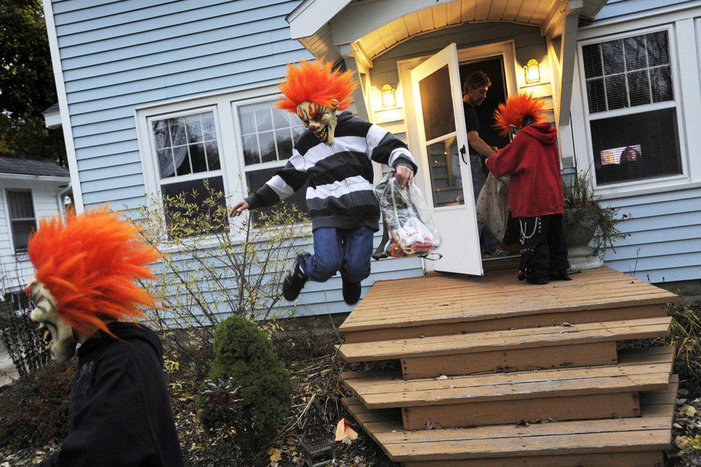 "Chris, 14, and Nikolus Johnston, 12, center, make the trick-or-treat rounds with their friend Jared Dionne, 13, right, on Halloween in Jackson. The three are dressed as Juggalos, as the fans of the music group Insane Clown Posse are known. ""We're all Juggalos."" Dionne said, adding, ""Well, mostly just me, but them too."""