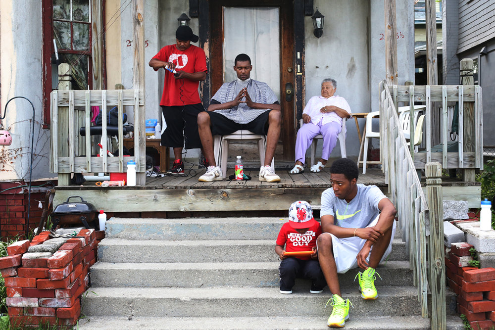 Abayomi Miller, left, gets his clippers ready to cut hair for his neighbor Jason Johnson, center, on Miller's front porch Wednesday, May 21, 2014 in North Toledo. With temperatures climbing into the low 80's, Darren McCadney, right, and his son Zavyn, 4, were also out in the sunshine. Mr. Miller said he often cuts hair for his family and neighbors.