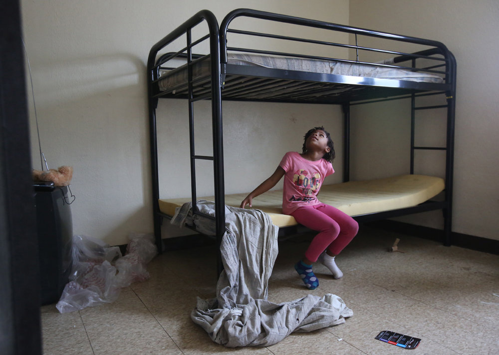 Relonna Alexander, 7, inspects her new bunk bed after it was delivered and assembled by volunteers from Extreme Results gym along with other donated furniture Friday, December 23, 2016, at Birmingham Terrace in East Toledo. Vincent Ceniceros, CEO of the gym, grew up in Birmingham Terrace and wanted to donate to someone at the complex for Christmas. He reached out to Rosalyn Koontz, whose neighbors know her as Ms. Toni Warren, a longtime resident of the complex to find a family in need. Ms. Koontz thought of Nakesha Phillips and her five children, including Relonna, who had been living in the complex for five months without any real furniture. Now, her children will have beds, a table to eat Christmas dinner and a couch to join their Christmas tree.