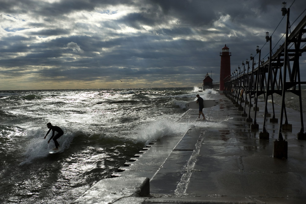Surfers take advantage of high waves generated by a storm over Lake Michigan to hit the waves at Grand Haven State Park. Surfers who brave the great lakes often take to the water when the waves are higher during the winter months.