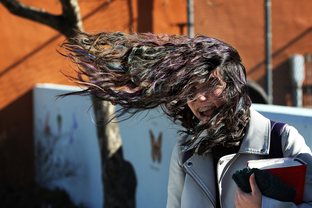 """I can't get my hair back!"" Mckayla Mejia, 15, laughed as she checked her phone after school Wednesday, March 8, 2017, in central Toledo. High winds swept through the greater Toledo area Thursday."