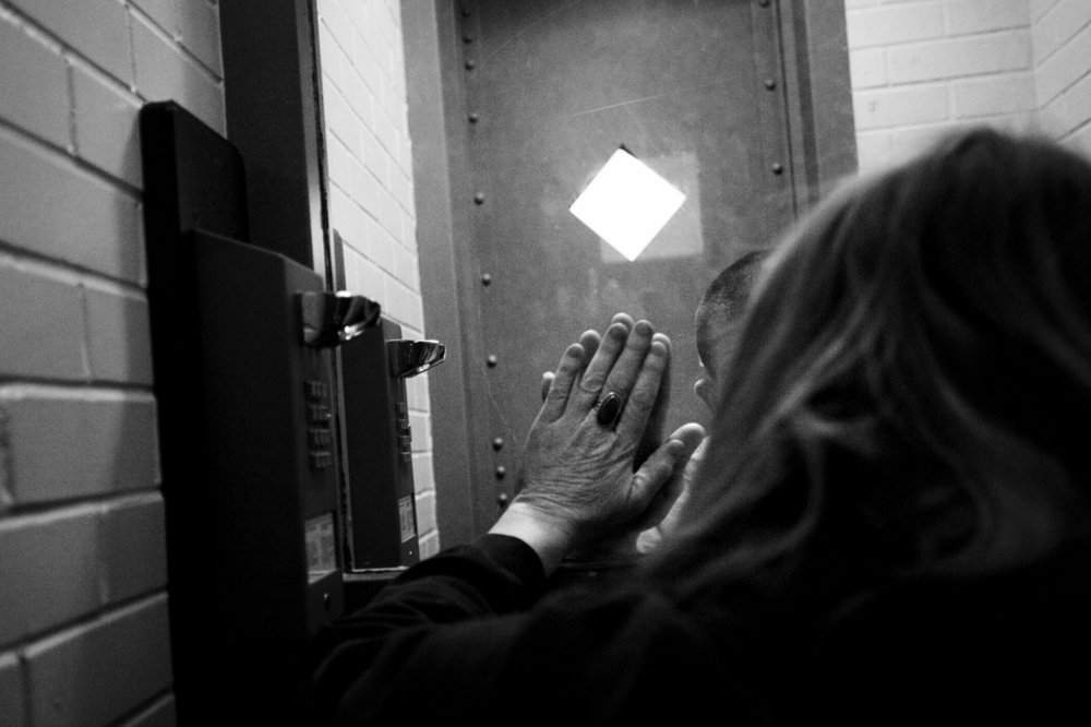 Gail Hammett holds her hand up to the glass in the Jackson County Jail on W. Wesley Street to match her son, James, who also raised his hand. Gail has been walking about two miles each way every Thursday since August to spend 15 minutes in county lockup visitation with her son. James Hammett was later sentenced to 19 to 40 years in prison after pleading guilty to first-degree home invasion, felonious assault and two felony weapons violations.