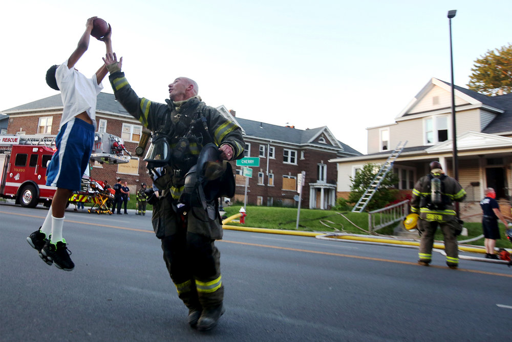 Lt. Pete Traver can't cover Tabari Triplett, 11, as he plays football with some friends from the neighborhood Monday, June 5, 2017, after Toledo firefighters had extinguished a blaze at a house on Cherry Street in Toledo. Battalion Chief Brent Wettle said the fire was reported at about 8:15 p.m. Monday evening in the 3300 block of Cherry Street, and caused an estimated $50,000 in damage. No injures were reported and the fire was under control within half an hour. The Red Cross was contacted to provide aid to seven residents of the house.