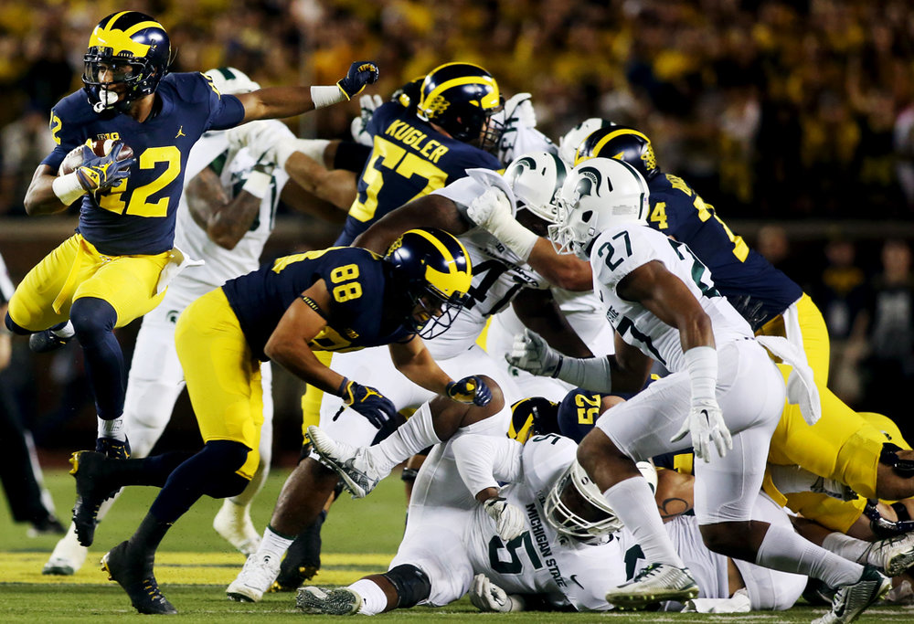 Michigan's Chris Evans (12) leaps over the Michigan State defense on the run in the first half of the Saturday, October 7, 2017, football match up at the Big House in Ann Arbor. Michigan State won, 14-10.