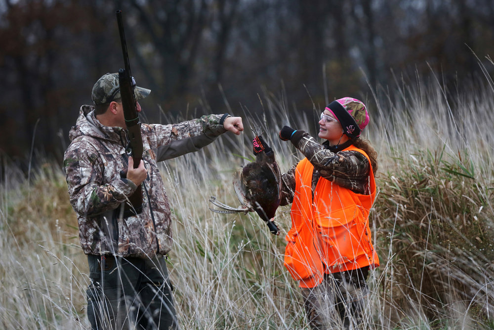 Nick Scholl, of Deerfield, left, congratulates his daughter Megan, 15, right, on bringing down her first pheasant while hunting Saturday, October 31, 2015, on land near Clinton, Mich. Megan and her sister Erika,18, were pheasant hunting for the first time as part of a youth hunt organized by Gene Merx, 79, who lives on the land. Both girls said that while hunting isn't particularly popular with their friends, they were excited to get into the sport.