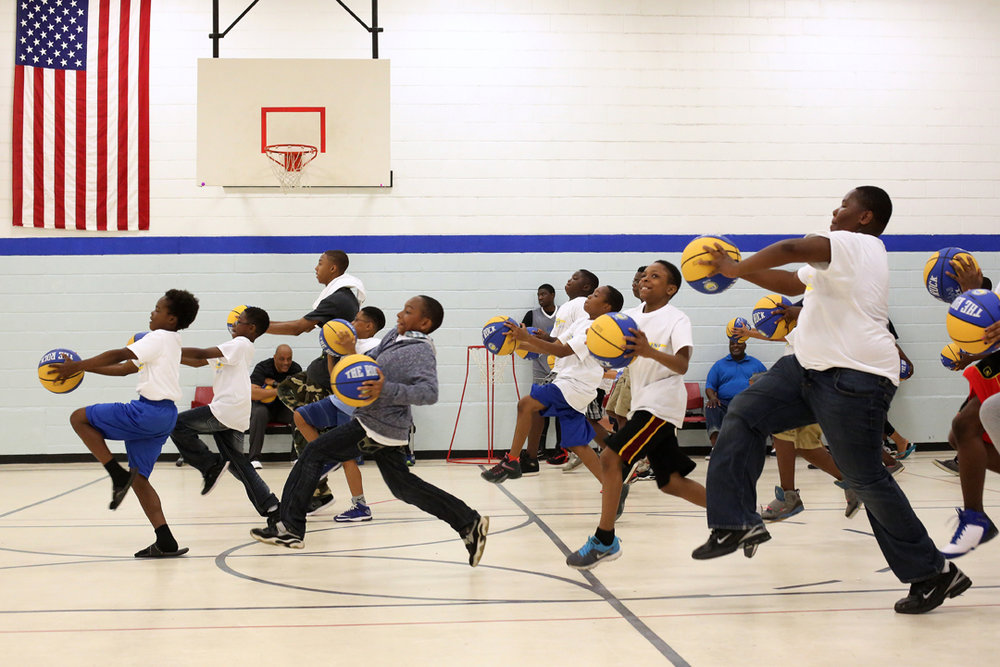Erian Gambriell, 12, left, leads the pack as he and other children run through basketball drills together during the 2015 Dribbling with Dads Initiative Saturday, June 20, 2015, at the Frederick Douglass Community Center in West Toledo. About 125 children attended the 1k walk, dribbling basketballs with their parents and families through the neighborhood around the Frederick Douglass Community Center. The event was organized by the Lucas County Metropolitan Housing Authority for the fourth year of their Fatherhood Initiative Celebration, held to recognize fathers and support male involvement in children's lives.
