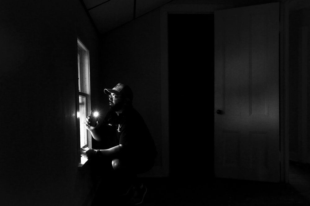 Albert Algerian, a Rochester Code Enforcement Officer, uses his phone light to check for flaking paint on a window during an inspection demonstration Thursday, June 22, 2017, at a rental home in Rochester, New York. A new Toledo law, based on Rochester's decade-old lead law, requires rental buildings built before 1978 with up to four units and day-care centers to be certified �lead-safe.�
