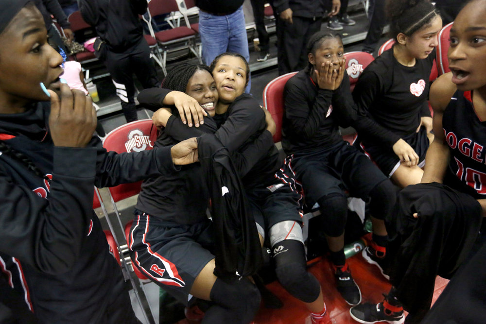 Rogers' Tanaziah Hines, center left, and Tasya Gant, center, right, embrace as their teammates celebrate after the Rams beat Gilmour Academy in the Saturday, March 17, 2018, OHSAA Division II state championship game at Value City Arena in Columbus. Rogers beat Gilmour Academy, 51-37, to win their first state championship.