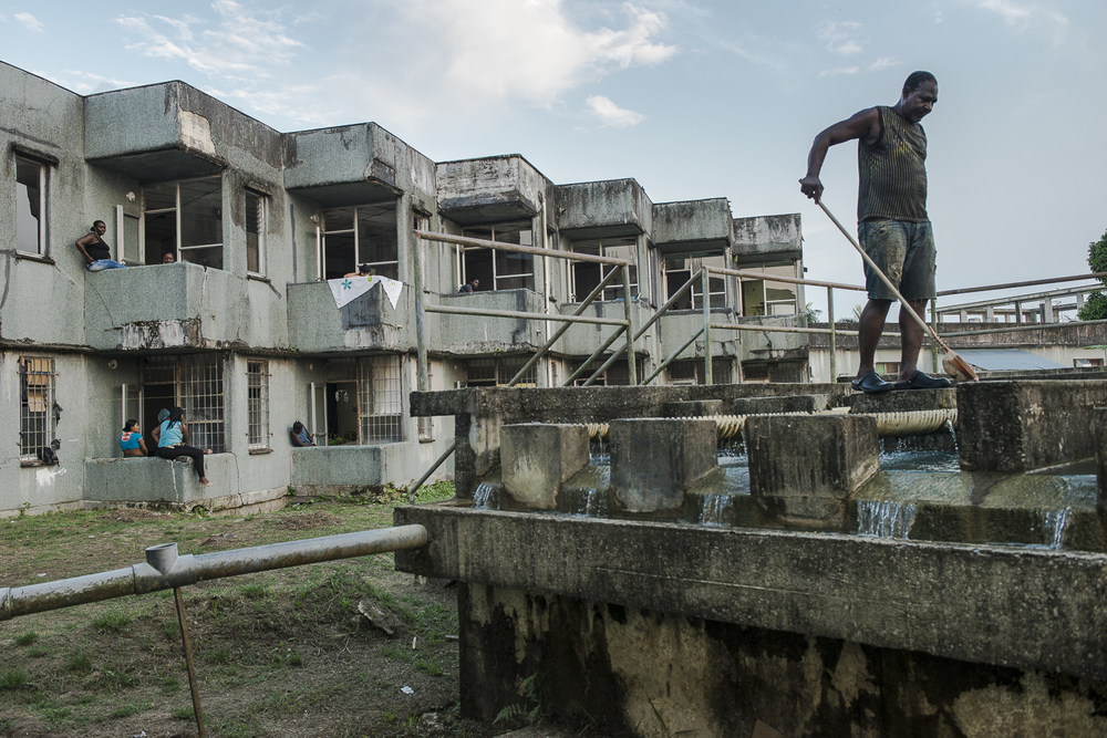 Back of the hospital. A man works on the water treatment station.