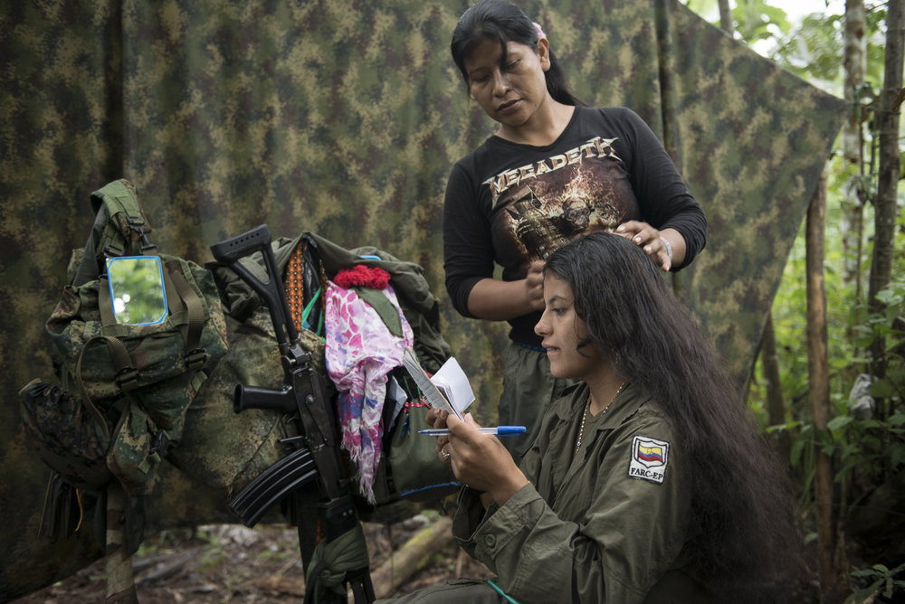 """May 2015, South Caquetá. While Sandra reviews the encoding of the messages she will send by radio to other groups or to the command, Jessica begins to plait her hair. Sandra has 8 years into the FARC-EP's ranks. She joined at 14 and she explains she was attracted by the lifestyle and the possibility to escape from the woman classic function in the countryside society. """"Find a husband? It's not a future"""", she says, """"and in addition, a responsible husband? No, they abandoned their pregnant wife, with one child… Here, with the FARC, we contribute to a just struggle."""" Jessica joined the FARC-EP at 18. She says she was seduced by the order and the female presence when a commander came to her school to present the guerilla. She also wanted to liberate her spot in the boarding school for her youngest sister."""