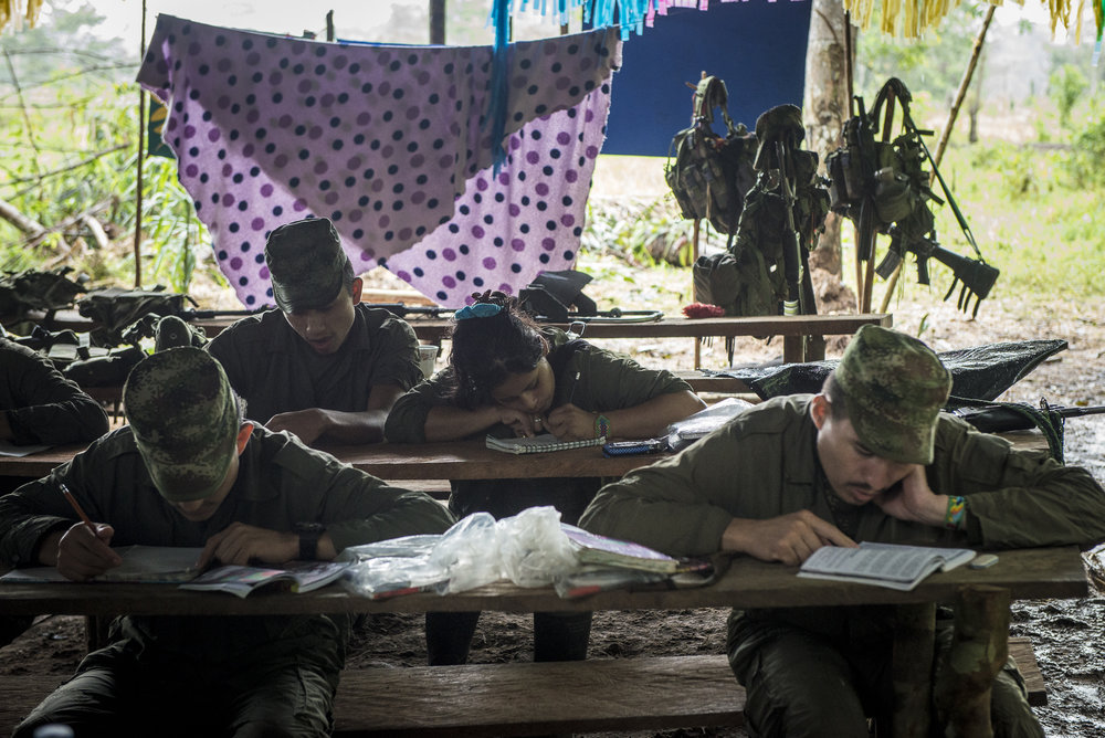 """July 2016, South Caqueta. A class where the guerrilleros are learning to read, write and count. It's quite common that they almost never had the opportunity to go to school. They come from very poor peasants family and had to work very young as """"jornalero"""", before choosing engage into the guerrilla. There, when the war was not so strong, they took some days to learn to write."""