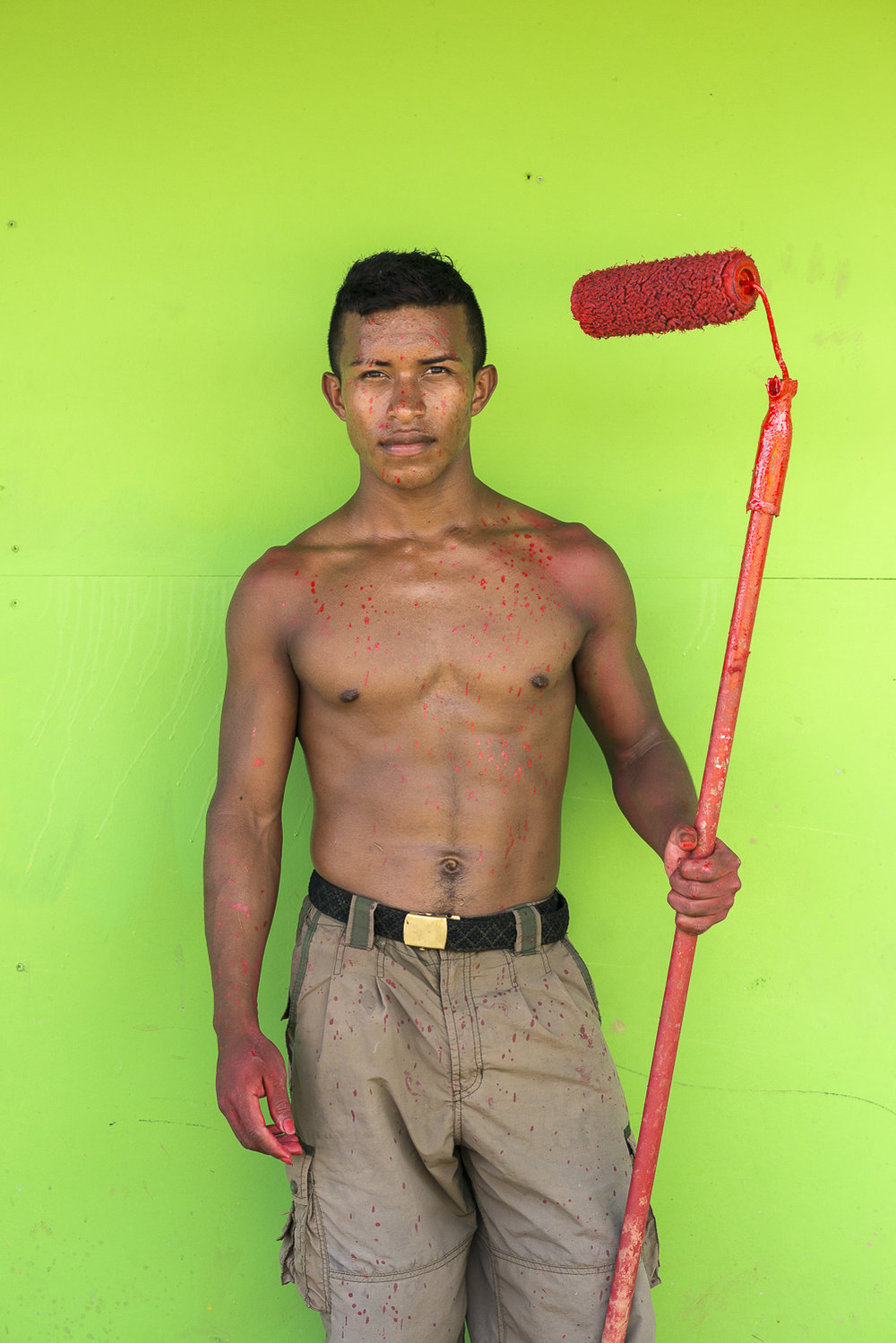 "Rorjelio is painting his home. ""I'm learning!' he says, because it's the first time in his life he uses a paintbrush."