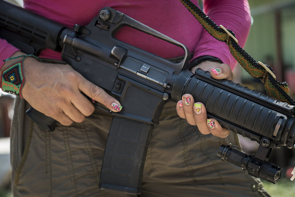 A guerrilla is posing with her weapon. As many other guerrilleras, she has a colorfull nail polish. Female combatants represents around 40% of the FARC troops. (January 27, 2016, Putumayo)
