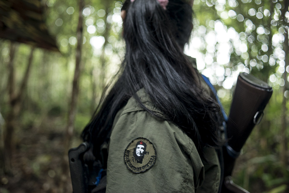 A female FARC combatant is looking forward. There is a patch on her arm with Che Guevara's face. (May 09, 2015. South Caquetá)