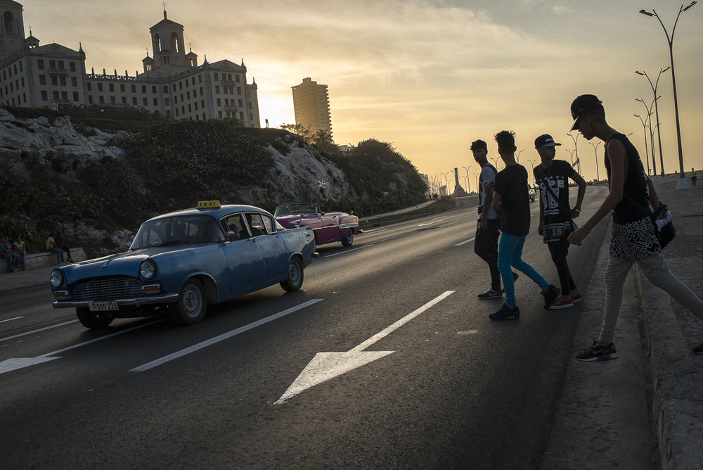 "March 27, 2016, La Habana. The road near the Malecón and the mythic National Habana Hotel receives the sunset light. Young Cubans are crossing the road while an old American car, a ""taxi colectivo"" is following its way. This typical old car is a symbol of the Cuban capital. It's also a living testimony of the economic embargo effects, with the prohibition to import recent cars. Few days ago on March 2016, the United States president Barack Obama went to Cuba for a historic visit. Since 1928, no US president ever travelled to the Caribbean island."